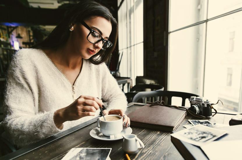 thoughtful-woman-stirs-sugar-cup-coffee